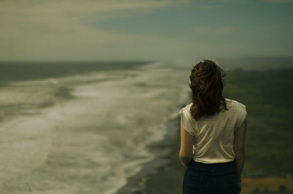Photo of a lady looking pensively at the ocean